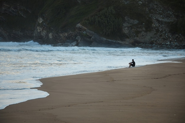 Surfer in wetsuit zittend aan de rand van een zandstrand onder een groene en rotsachtige heuvel in de avond Gratis Foto