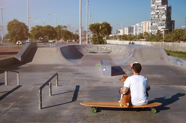 Surfer zit op een longboard in een skatepark van de stad en knuffelt zijn bruine en witte basenji-hond, kijkend naar het stadslandschap, schot vanaf de achterkant Gratis Foto