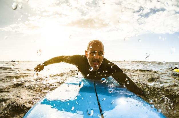 Surferkerel die met surfplank bij zonsondergang in tenerife paddelt Premium Foto