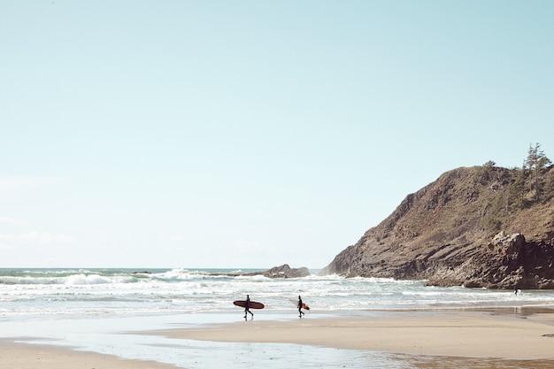 Surfers in de verte op rotsstrand Gratis Foto