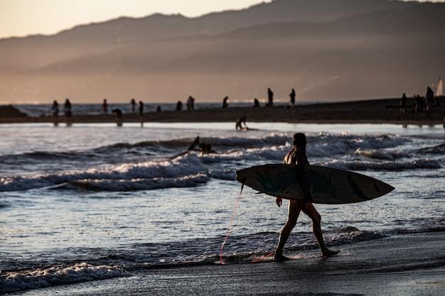 Surfersilhouet die door het overzees bij zonsondergang lopen Gratis Foto