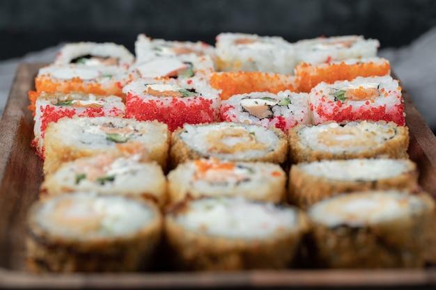 Sushi ingesteld op een houten bord met gemengde ingrediënten. Gratis Foto