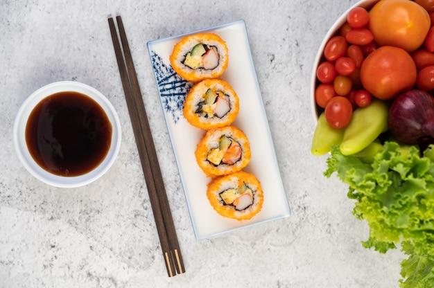 Sushi is in een bord met stokjes en dipsaus op een witte cementvloer. Gratis Foto
