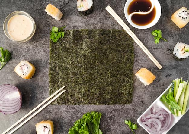 Sushi met ingrediënten en eetstokjes horizontaal kader Gratis Foto