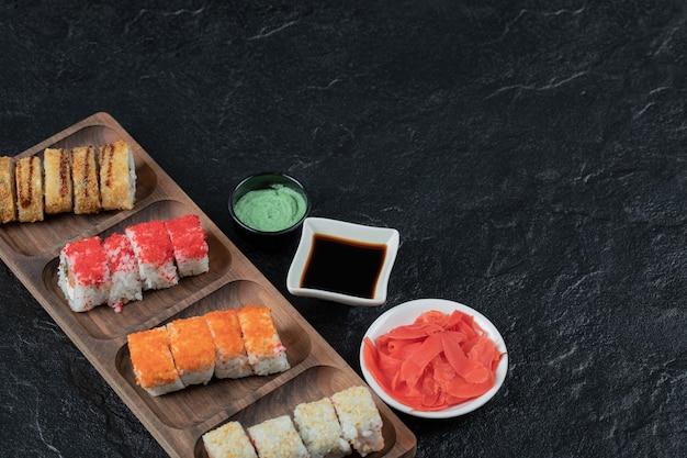Sushi op een houten bord met wasabi, gember en sojasaus. Gratis Foto