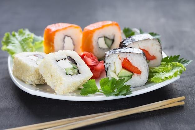 Sushi op een vierkant wit bord met peterselie greens met stokken op de voorgrond. grijs Premium Foto