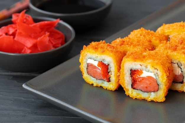 Sushi roll gebakken in tempura op zwarte plaat close-up Premium Foto