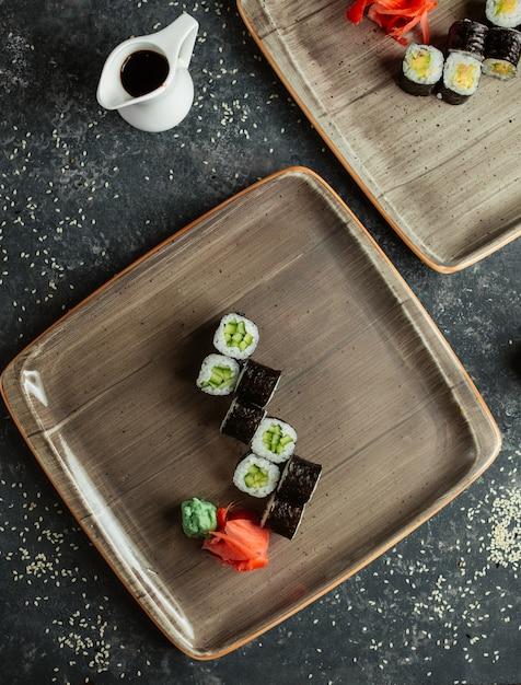 Sushi rolletjes met komkommer geserveerd met gember en wasabi Gratis Foto