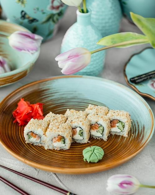 Sushi rolletjes met zalm, roomkaas, cucuber bedekt met sesam Gratis Foto