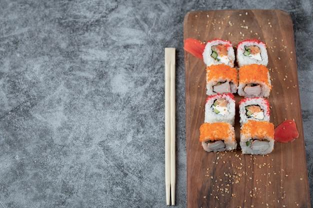 Sushi rolt met zeevruchten en rode kaviaar geïsoleerd op een houten schotel. Gratis Foto