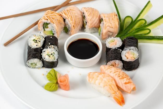 Sushi set met sojasaus in het midden van een bord en eetstokjes Gratis Foto