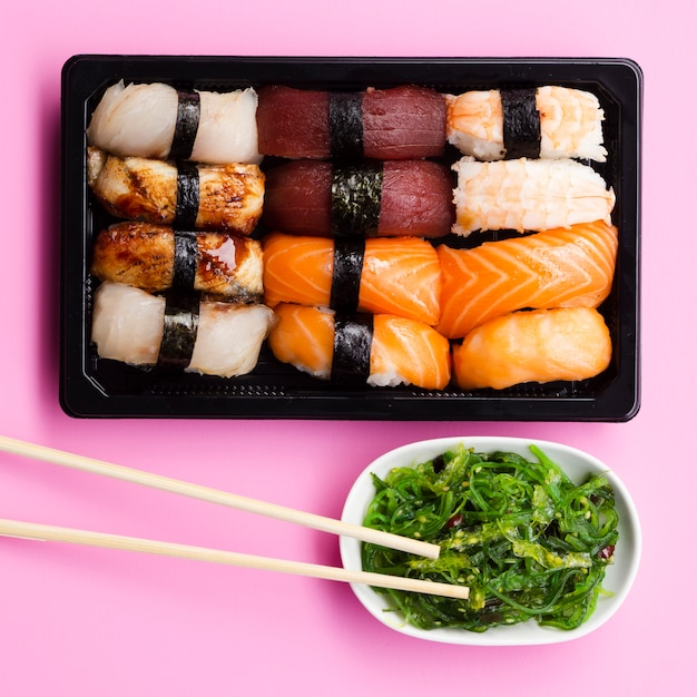 Sushi vastgestelde doos met zeewiersalade op een roze achtergrond Gratis Foto