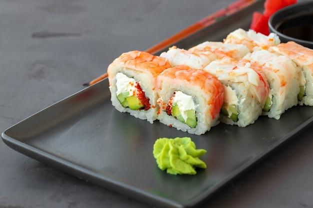 Sushibroodje bedekt met garnalenvlees op zwarte ceramische plaat dichte omhooggaand Premium Foto