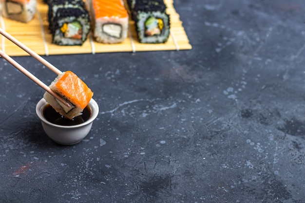 Sushibroodje met zalm met eetstokjes over een kom met sojasaus op een donkere tafel. traditioneel japans eten. Premium Foto