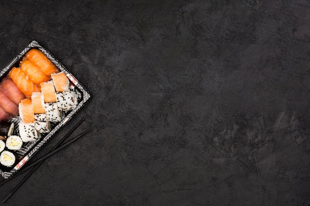 Sushibroodje op dienblad en eetstokjes over donkere geweven oppervlakte met ruimte voor tekst wordt geplaatst die Gratis Foto