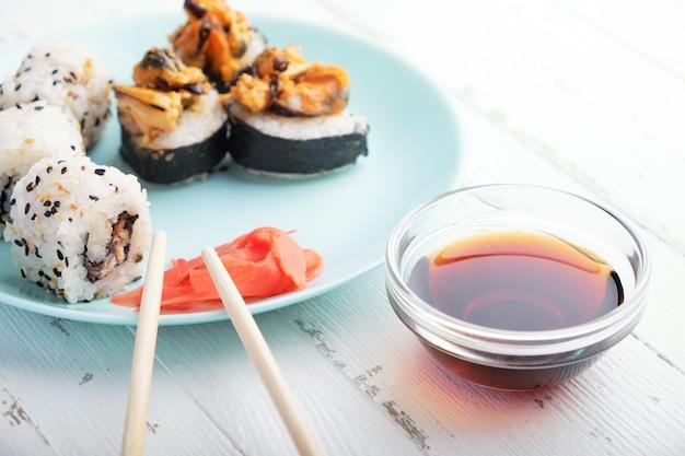 Sushibroodjes in blauw bord, eetstokjes en sojasaus Premium Foto