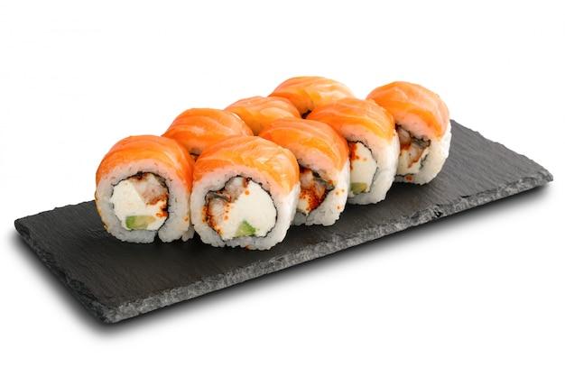 Sushibroodjes met paling, zalm, avocado, vliegende vissenkaviaar en roomkaas binnen geïsoleerd op wit Premium Foto