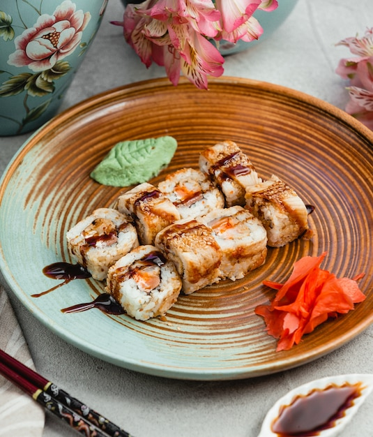 Sushibroodjes met sojasaus binnen bruine blauwe plaat. Gratis Foto