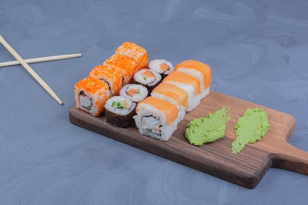 Sushibroodjes met wasabisaus op een houten schotel Gratis Foto