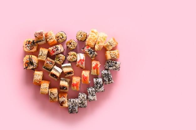 Sushireeks en broodjes dienden als hart op roze. valentijnsdag eten. uitzicht van boven. kopieer ruimte. levering op feestdagen. Premium Foto
