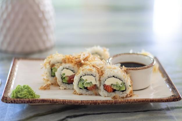 Sushirolletjes met zalm, komkommer en philadelphia roomkaas op marmeren tafel met kopie ruimte. sushi menu. japans eten. Premium Foto