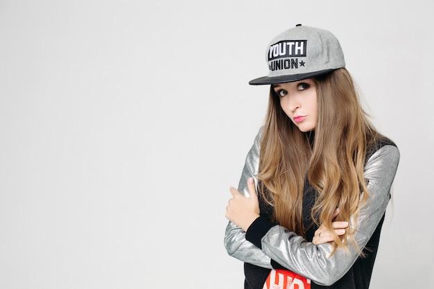 Swag stijlvolle tienermeisje in cap poseren met handen omhoog. Premium Foto