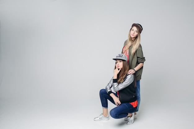 Swag-vriendinnen hipster in stijlvolle slijtage en petten op het hoofd. Premium Foto