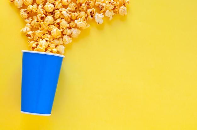 Sweet caramel popcorn in blauwe papieren emmer. Premium Foto