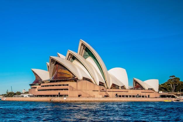 Sydney opera house in de buurt van de prachtige zee onder de heldere blauwe hemel Gratis Foto