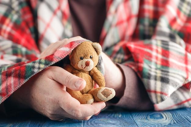 Symbool van zorg, mannelijke hand houden beer speelgoed Premium Foto