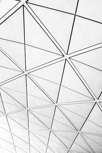 Symmetrisch driehoekspatroon op vensters met uitzicht op een grijze bewolkte hemel Gratis Foto