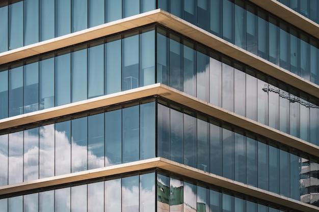Symmetrisch zicht op de hoek van een kantoorgebouw met verticale beglazing Premium Foto