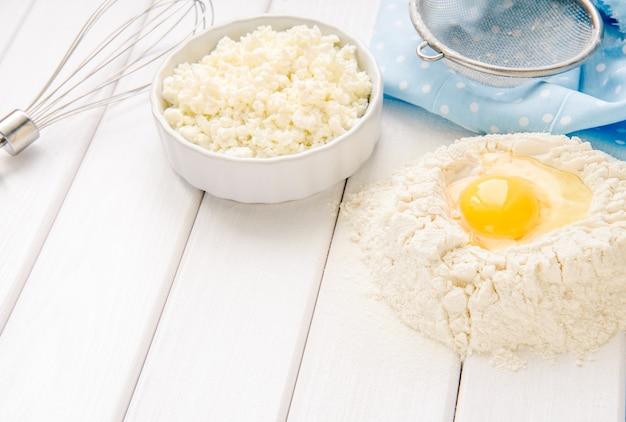 Taart bakken in rustieke keuken - deeg recept ingrediënten eieren, bloem, melk, boter, suiker op witte planken houten tafel van bovenaf Premium Foto
