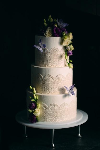 Taart is versierd met bloemen op donker Premium Foto