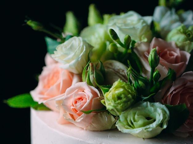 Taart is versierd met bloemen op een donkere. Premium Foto