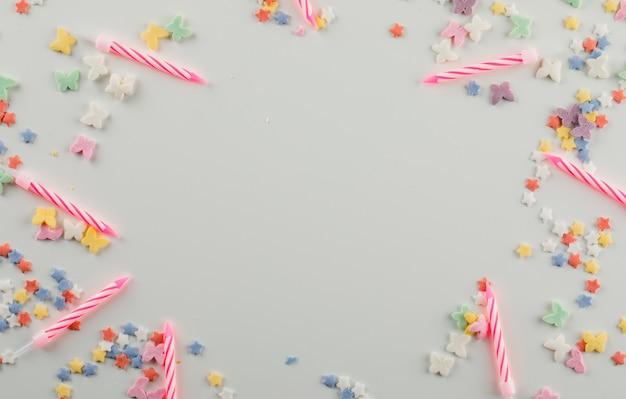 Taart kaarsen met zoete hagelslag op een witte tafel Gratis Foto