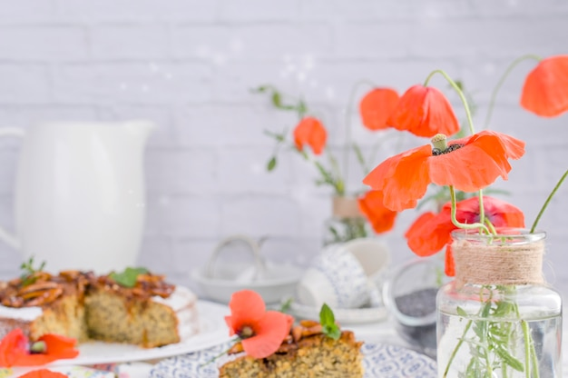 Taart met maanzaad op een witte achtergrond. huisgemaakt gebak en rode bloemen Premium Foto