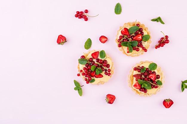 Taartjes met aardbeien, bessen en slagroom versierd met muntblaadjes, bovenaanzicht Premium Foto