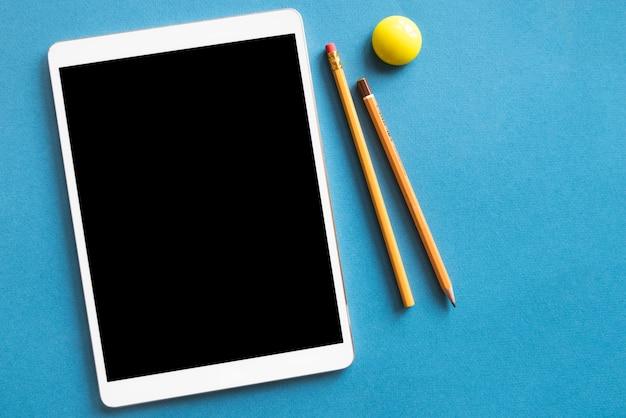 Tablet en potloden op blauwe oppervlak Gratis Foto