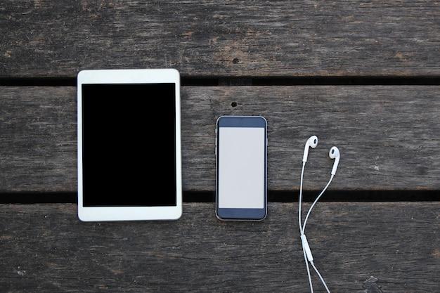Tablet en smartphone met hoofdtelefoon op oude houten tafel foto
