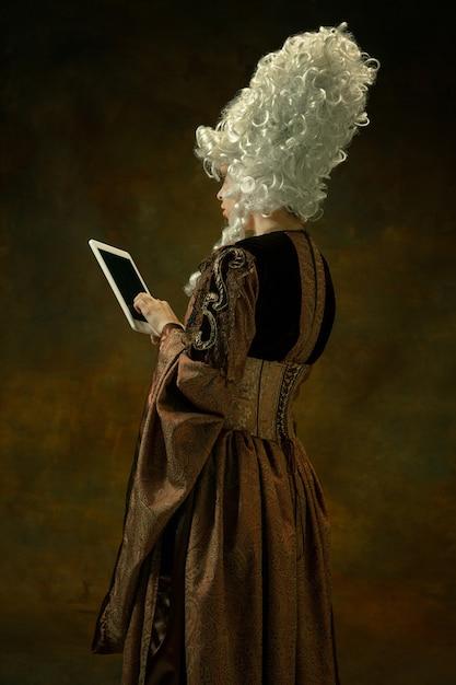 Tablet gebruiken om online te zijn. portret van middeleeuwse jonge vrouw in bruine vintage kleding op donkere muur. vrouwelijk model als hertogin, koninklijk persoon. concept vergelijking van moderne tijdperken, mode. Gratis Foto