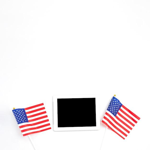 Tablet geplaatst tussen amerikaanse vlaggen Gratis Foto