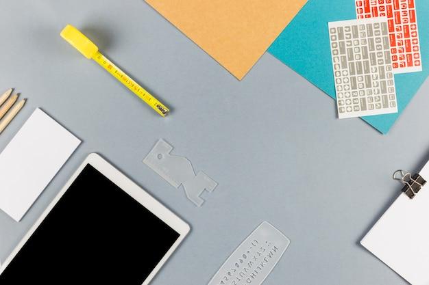 Tablet in de buurt van papier met clip, kaartjes, potloden en meetlint Gratis Foto