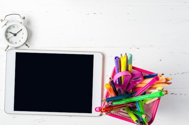 Tablet met een leeg scherm en kantoorbenodigdheden op een witte houten achtergrond. concept app voor schoolkinderen of online leren voor kinderen. kopieer ruimte Premium Foto