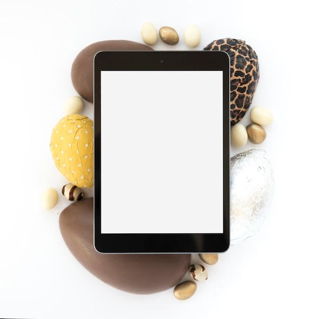 Tablet met leeg scherm op chocolade paaseieren Gratis Foto
