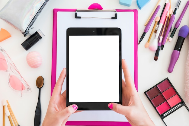 Tablet omringd door make-up Gratis Foto