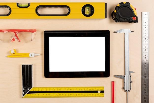 Tablet op architectenbureau met hulpmiddelenmodel Gratis Foto