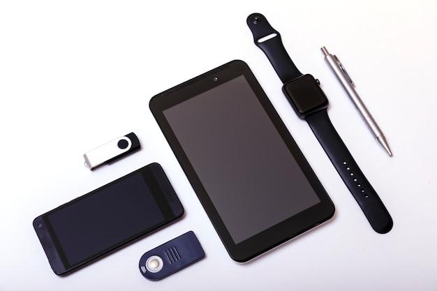 Tablet, telefoon, pendrive, pennen, horloge op wit Premium Foto