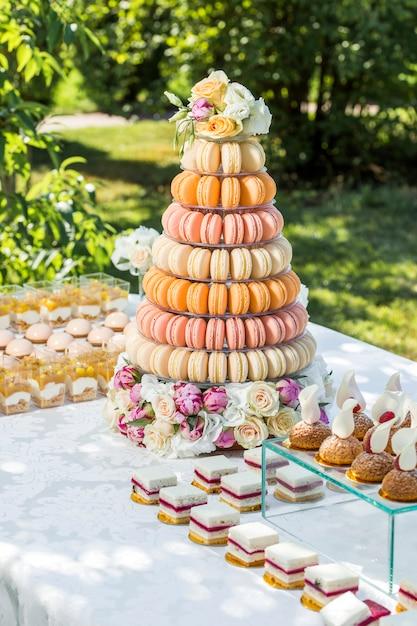 Tafel met snoep versierd met bloemen en macaron cake Premium Foto