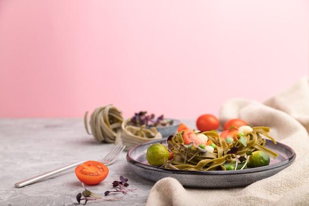 Tagliatelle groene spinazie pasta met tomaat, erwt en microgroene spruitjes. zijaanzicht, kopieer ruimte. Premium Foto